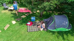 Aerial top view of campsite from above, mother and daughter having fun, tent and camping equipment under tree, family vacation. In camp outdoors concept stock image