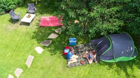 Aerial top view of campsite from above, mother and daughter having fun, tent and camping equipment under tree, family vacation. In camp outdoors concept royalty free stock image