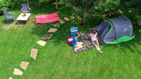 Aerial top view of campsite from above, mother and daughter having fun, tent and camping equipment under tree, family vacation. In camp outdoors concept royalty free stock photo