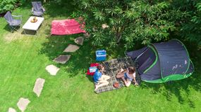 Aerial top view of campsite from above, mother and daughter having fun, tent and camping equipment under tree, family vacation. In camp outdoors concept royalty free stock photos