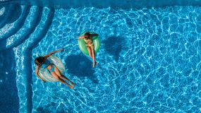 Aerial top view of children in swimming pool from above, happy kids swim on inflatable ring donuts and have fun in water. On family vacation royalty free stock photography