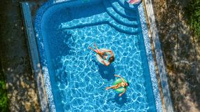 Aerial top view of children in swimming pool from above, happy kids swim on inflatable ring donuts and have fun in water. On family holiday vacation on resort stock photos