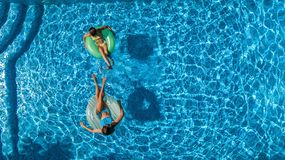 Aerial top view of children in swimming pool from above, happy kids swim on inflatable ring donuts and have fun in water. On family holiday vacation on resort royalty free stock photos