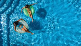Aerial top view of children in swimming pool from above, happy kids swim on inflatable ring donuts and have fun in water. On family holiday vacation on resort royalty free stock images
