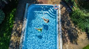 Aerial top view of children in swimming pool from above, happy kids swim on inflatable ring donuts and have fun in water. On family vacation stock photo