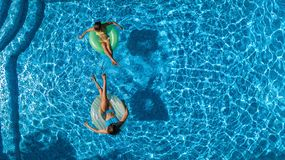 Aerial top view of children in swimming pool from above, happy kids swim on inflatable ring donuts and have fun in water. On family vacation stock images