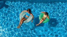 Aerial top view of children in swimming pool from above, happy kids swim on inflatable ring donuts and have fun in water. On family vacation stock photography