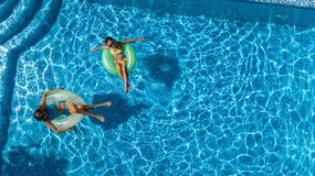 Aerial top view of children in swimming pool from above, happy kids swim on inflatable ring donuts and have fun in water. On family holiday vacation on resort stock photo
