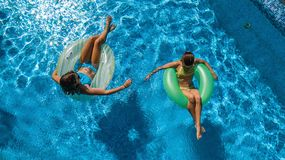 Aerial top view of children in swimming pool from above, happy kids swim on inflatable ring donuts and have fun in water. On family holiday vacation on resort stock photography