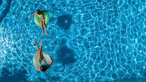 Aerial top view of children in swimming pool from above, happy kids swim on inflatable ring donuts and have fun in water. On family holiday vacation on resort royalty free stock photo
