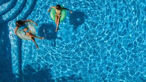 Aerial top view of children in swimming pool from above, happy kids swim on inflatable ring donuts and have fun in water. On family holiday vacation on resort stock images