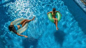 Aerial top view of children in swimming pool from above, happy kids swim on inflatable ring donuts in water on family. Aerial top view of children in swimming royalty free stock photography