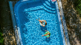 Aerial top view of children in swimming pool from above, happy kids swim on inflatable ring donuts in water on family. Aerial top view of children in swimming royalty free stock images