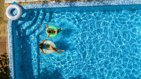 Aerial top view of children in swimming pool from above, happy kids swim on inflatable ring donuts in water on family Stock Photo
