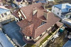 Aerial top view of complex house metal shingle roof and high brick chimneys. Roofing, construction, repair and renovation work.  stock images