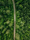 Aerial top view of a country road through a fir forest in summer rural Finland Royalty Free Stock Images