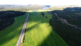 Aerial top view of a country road through a green rural field royalty free stock photo