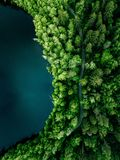 Aerial top view of country road in green summer forest and blue lake. Rural landscape in Finland stock photo
