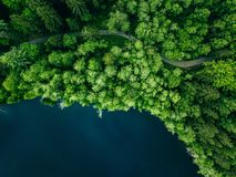 Aerial top view of country road in green summer forest and blue lake. Rural landscape in Finland royalty free stock photography
