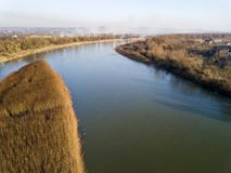 Aerial top view, countryside panorama of quiet river water and island with dry grass, misty horizon under blue sky on sunny day. Drone photography stock photos