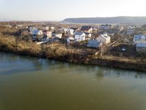 Aerial top view, countryside panorama of residential houses on river bank on blue sky and woody hill background. Drone photography.  stock photo