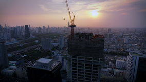 Aerial top view at crane construction working and bangkok city area at twilight sunset, tilt up shot, High quality footage 4K stock video