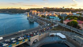 Aerial top view of Dnieper river and Podol district skyline from above, traffic jam on road, sunset in Kiev city, Ukraine Royalty Free Stock Image