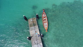 Aerial top view drone photo of floating boat on water surface and pier on Rawai beach in Phuket stock image