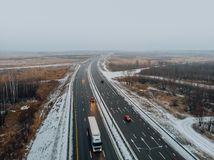Aerial or top view from drone to winter asphalt highway or motorway road in countryside with car and truck traffic driving fast.  royalty free stock photography