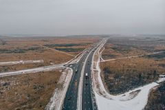 Aerial or top view from drone to winter asphalt highway or motorway road in countryside with car and truck traffic driving fast.  stock photo