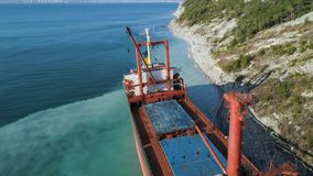 Aerial top view of an empty, red barge moored near the beautiful blue sea shore. Big Industrial ship standing near the stock images