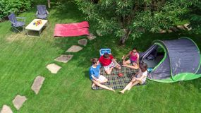 Aerial top view of family in campsite from above, parents and kids relax and have fun in park, tent and camping equipment. Under tree, family vacation in camp stock image