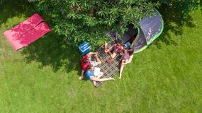 Aerial top view of family in campsite from above, parents and kids relax and have fun in park, tent and camping equipment. Under tree, family vacation in camp royalty free stock images