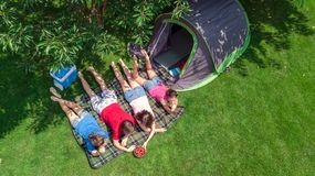 Aerial top view of family in campsite from above, parents and kids relax and have fun in park, tent and camping equipment. Under tree, family vacation in camp royalty free stock photo