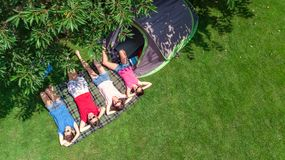 Aerial top view of family in campsite from above, parents and kids relax and have fun in park, tent and camping equipment. Under tree, family vacation in camp stock images