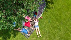 Aerial top view of family in campsite from above, parents and kids relax and have fun in park, tent and camping equipment. Under tree, family vacation in camp royalty free stock image