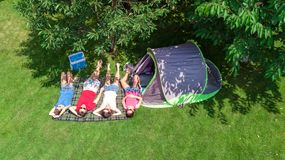 Aerial top view of family in campsite from above, parents and kids relax and have fun in park, tent and camping equipment. Under tree, family vacation in camp stock photo
