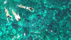 Aerial top view of family snorkeling from above, mother and kids snorkelers swimming in a clear tropical sea water with corals stock image