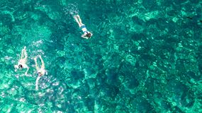 Aerial top view of family snorkeling from above, mother and kids snorkelers swimming in a clear tropical sea water with corals royalty free stock photo