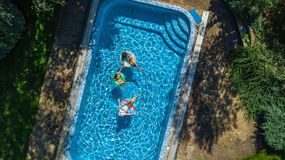 Aerial top view of family in swimming pool from above, happy mother and kids swim on inflatable ring donuts and have fun in water Stock Photos