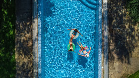Aerial top view of family in swimming pool from above, happy mother and kids swim on inflatable ring donuts and have fun in water Stock Photo