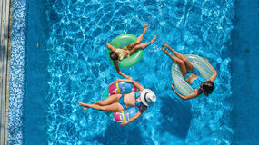 Aerial top view of family in swimming pool from above, happy mother and kids swim on inflatable ring donuts and have fun in water Royalty Free Stock Photo