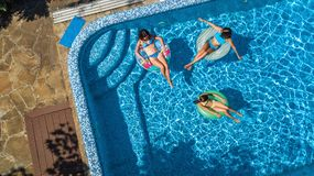 Aerial top view of family in swimming pool from above, happy mother and kids swim on inflatable ring donuts and have fun in water. On family vacation, tropical Royalty Free Stock Photos