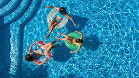 Aerial top view of family in swimming pool from above, happy mother and kids swim on inflatable ring donuts and have fun in water. On family vacation, tropical Royalty Free Stock Images