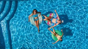 Aerial top view of family in swimming pool from above, happy mother and kids swim on inflatable ring donuts and have fun in water. On family vacation, tropical Stock Photos