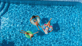 Aerial top view of family in swimming pool from above, happy mother and kids swim on inflatable ring donuts and have fun in water Stock Images