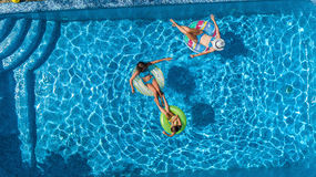 Aerial top view of family in swimming pool from above, happy mother and kids swim on inflatable ring donuts and have fun in water Stock Image