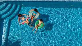 Aerial top view of family in swimming pool from above, mother and kids swim and have fun in water on family vacation. In hotel resort royalty free stock photos