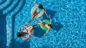 Aerial top view of family in swimming pool from above, mother and kids swim on inflatable ring donuts and have fun in water Stock Images