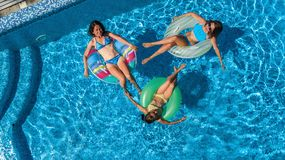 Aerial top view of family in swimming pool from above, mother and kids swim on inflatable ring donuts and have fun in water. Aerial top view of family in Stock Photos